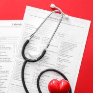 stetoskop na formularzach badań na czerwonym biurku