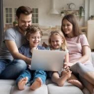rodzina kobieta mężczyzna dwójka dzieci siedzący na sofie z komputerem na kolanach