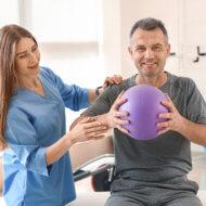 mężczyzna w szarym stroju podczas rehabilitacji trzymający fioletową piłkę i stojąca obok rehabilitantka