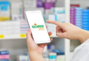 zdjęcie telefonu z grafiką na ekranie z Olmed apteki on-line trzymanego przez farmaceutę