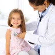 małą dziewczynka podczas osłuchiwania przez lekarza
