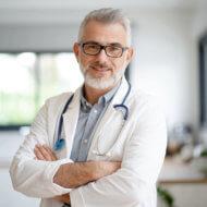 lekarz z siwą brodą w białym kitlu i stetoskopem na szyi