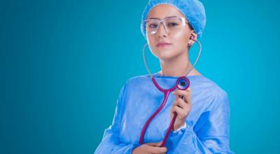 lekarz kobieta w niebieskim stroju chirurgicznym trzymająca różowy stetoskop