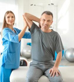 rehabilitantka podczas rehabilitacji ręki mężczyzny